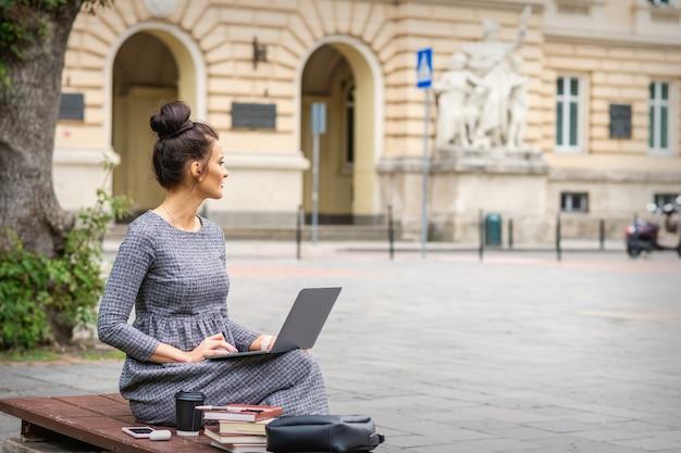学生の若い女性は大学の近くの街の通りのベンチでラップトップを使用します