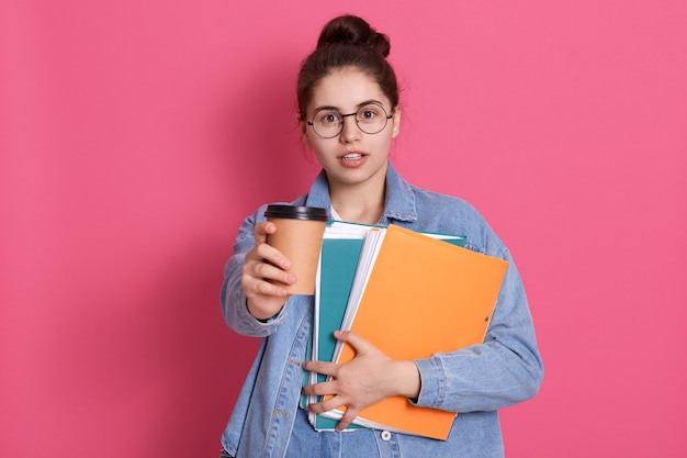 Student young woman with dark hair offers takeaway coffee, holding paper folder in hands