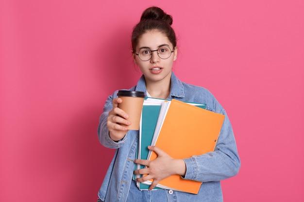 Studente giovane donna con i capelli scuri offre caffè da asporto, con in mano una cartella di carta