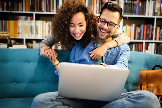Студенты вместе учатся в библиотеке. пара, учеба, технологии, концепция любви образования