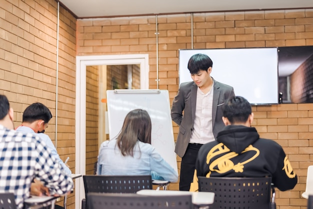 Students are taking exams to collect grades at the end of the semester and there is a young teacher supervising the exams in the classroom.