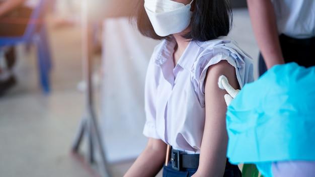 학생들은 학교에서 코로나 바이러스 또는 covid-19에 대한 예방 접종을 받고 있습니다.