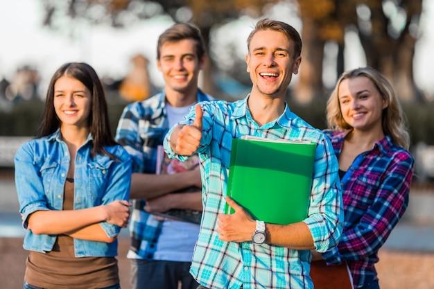 学生は公園を歩いていて親指を現しています。