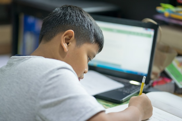 Students are writing books during online distance learning with computer notebook.