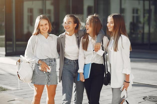 Студенты в кампусе с книгами и сумками