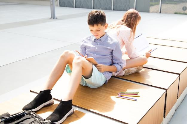 Студенты делают домашнее задание, сидя спиной к спине на школьном дворе кампуса. дружба подростков