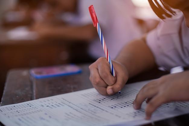 試験解答用紙を行う学生は、ストレスのある学校の教室で練習します。