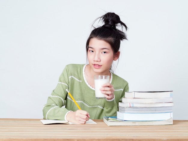 Students drink milk while doing homework.