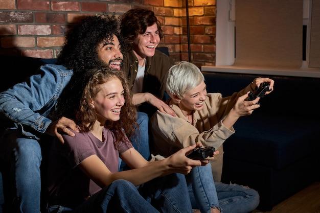 ビデオgam.friendsで遊ぶことを楽しんでいる学生はゲーム中に楽しんでいます、興奮したミレニアル世代の多様なアメリカ人の友人はリビングルームのインテリアでジョイスティックを楽しんでいます