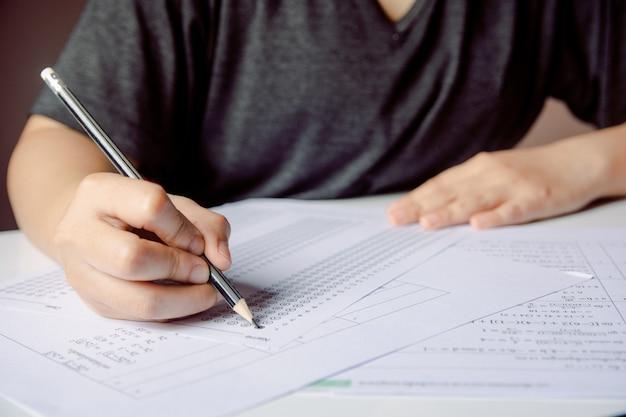 アンサーシートと数学の質問シートに選択した選択肢を書く鉛筆を持つ学生の手