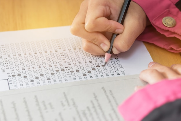 Students hands taking exams writing in examination room holding pencil on optical form