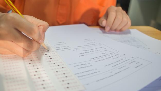 Students hands taking exams, writing examination room
