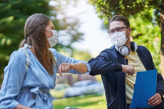 コロナウイルスのパンデミックにより、保護マスクを着用し、距離を置いてキャンパスでぶらぶらしている学生