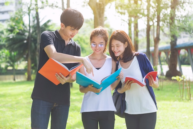 Students holding books and talking while standing in park. education in school or universi