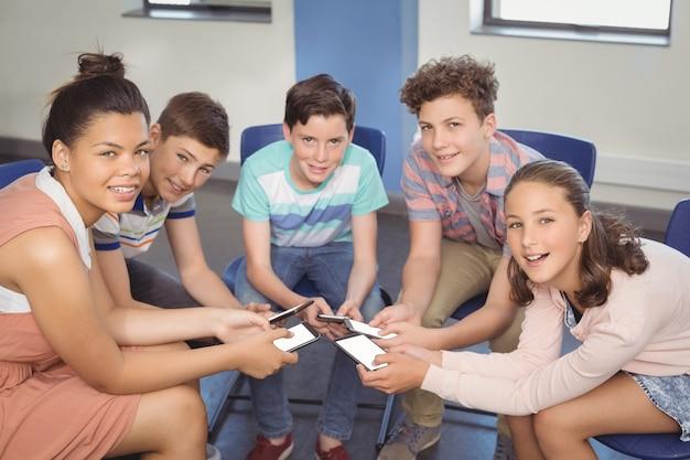 教室で携帯電話を持つ学生