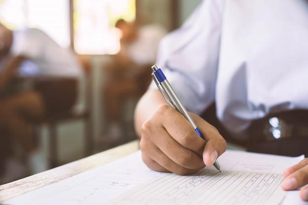 Студенты держа ручку в руке делая экзамены отвечают листам упражнений в классе с стрессом.