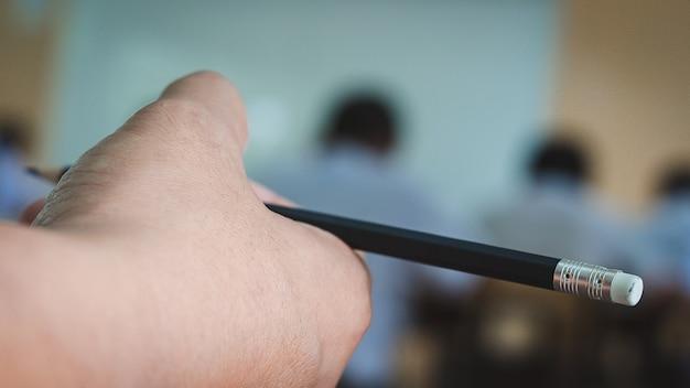 Студенты держат карандаш и читают упражнения на листах с ответами в классе школы со стрессом