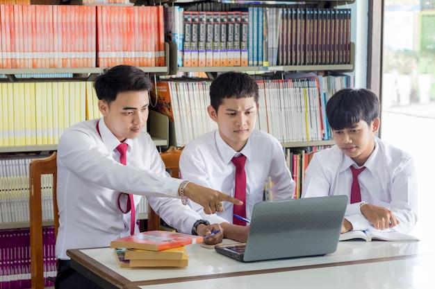Студенты в университете, работающие на компьютере в библиотеке