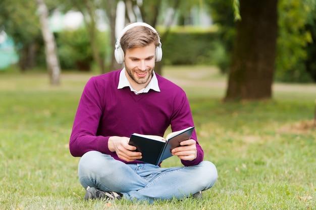 Студенческая жизнь. образование с электронной книгой. улыбающийся человек в наушниках, слушая музыку, пока читал книгу. парень открытый блокнот для заметок. получить полезную информацию. человек любит читать.