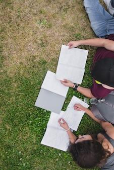 ノートを勉強している芝生に横たわっている学生