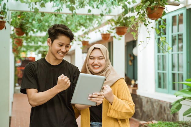 Students male and hijab girl happy when looking to the screen of the tablet