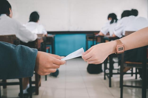 Студенты тайно передают друг другу записки во время урока