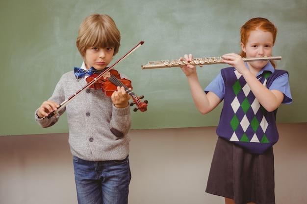 教室でフルートとバイオリンを学ぶ生徒