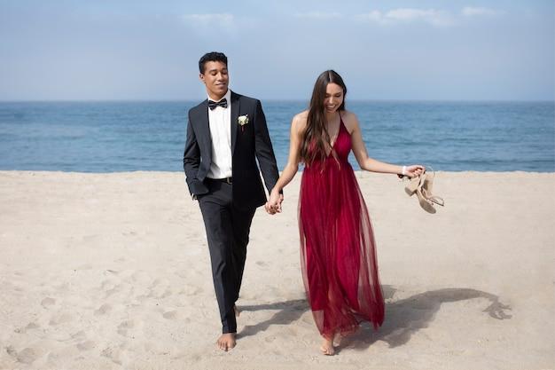 Studenti in abiti da ballo in spiaggia