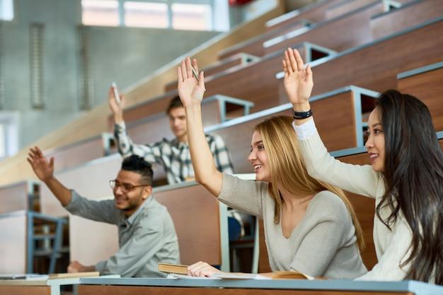 Студенты поднимают руки в классе