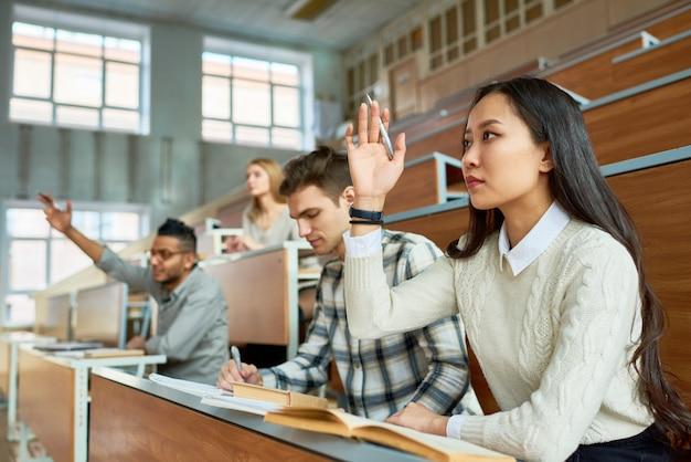 Студенты поднимают руки в колледже