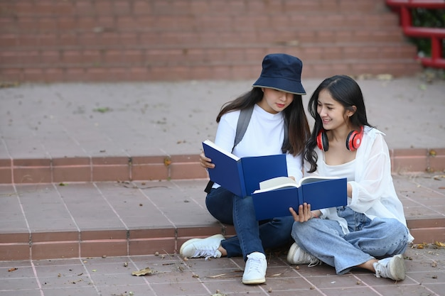 Студенты читают интересную книгу и готовятся к экзамену, сидя вместе в кампусе.
