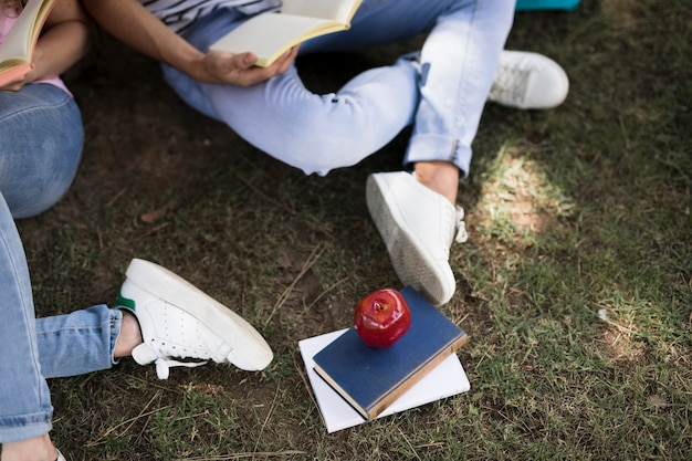 Students reading notebooks while sitting on grass
