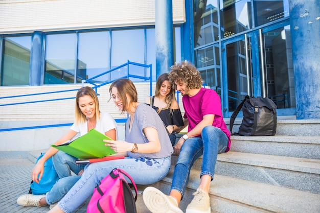 Students reading textbooks on steps near university