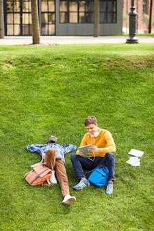緑の芝生でリラックスした学生