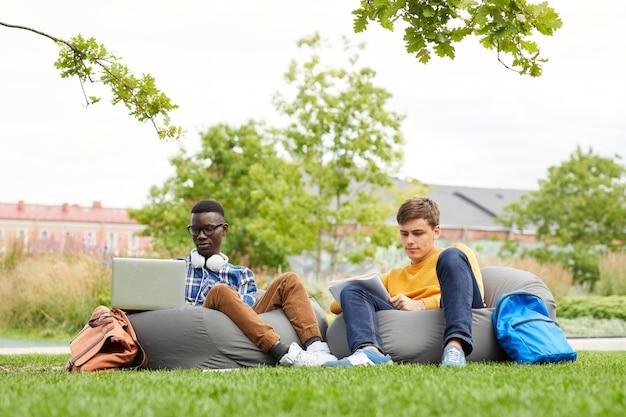キャンパスの屋外でリラックスした学生