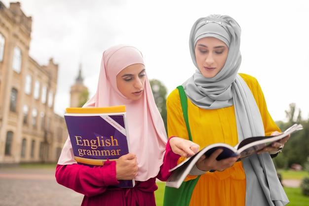 영어를 반복하는 학생. 수업에 걸어가는 동안 영어를 반복하는 바쁜 국제 무슬림 학생들