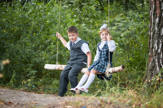 Students ride on the swing after school in school uniform.