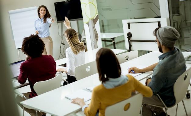 ワークショップ研修中に質問に答えるために手を挙げている学生 Premium写真