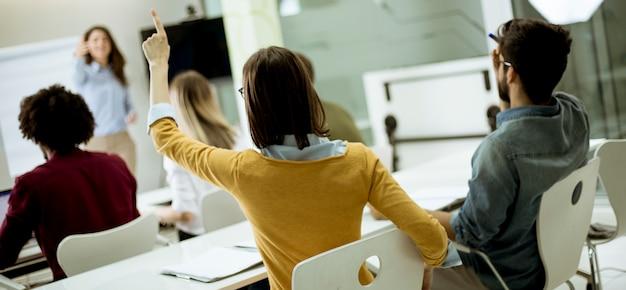 워크샵 훈련 중 질문에 대답하기 위해 손을 올리는 학생들