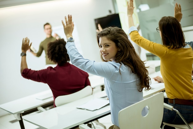 ワークショップ研修中に質問に答えるために手を挙げている学生