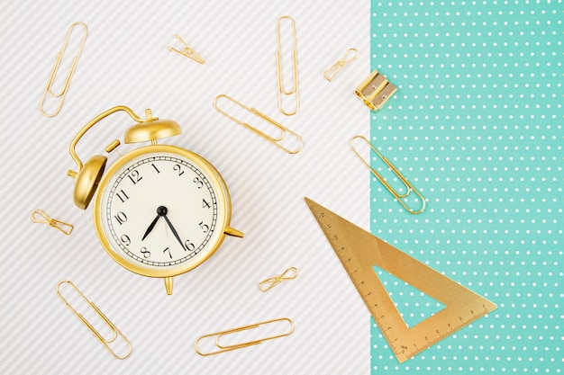 Students and school golden supplies with alarm clock. back to school and office stationery idea