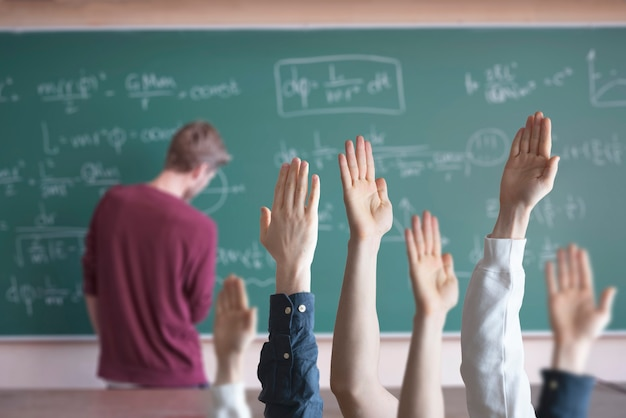 The students at school with raised handsãƒâƒã'âãƒâ'ã'â± classroom learning together