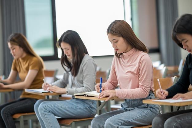 학생들은 대학 교실 책상에 앉아 시험을 치릅니다.