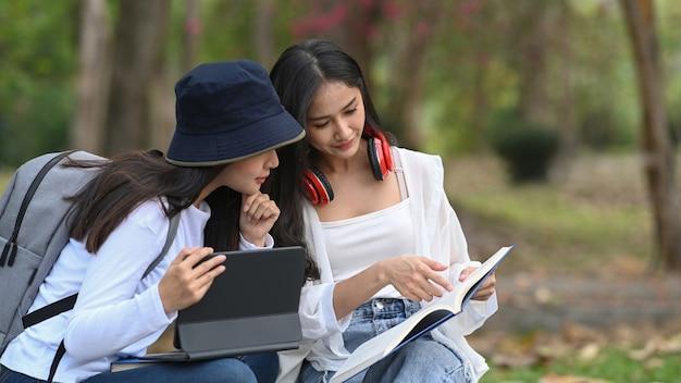 Студенты сидят на скамейке в парке, используют планшетный компьютер и читают книгу, готовятся к экзамену.