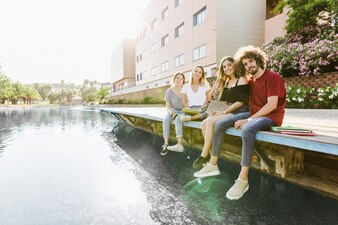 Students sitting in campus with lake