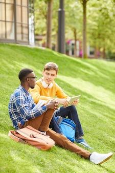 Студенты сидят на зеленой лужайке