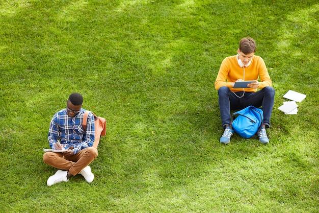 キャンパス内の芝生に座っている学生
