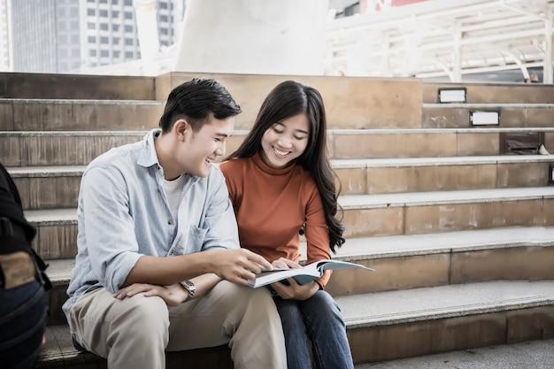 学生は大学に行く途中で読書を一緒に座っています。