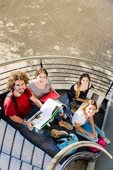 Students sitting with books on stairs