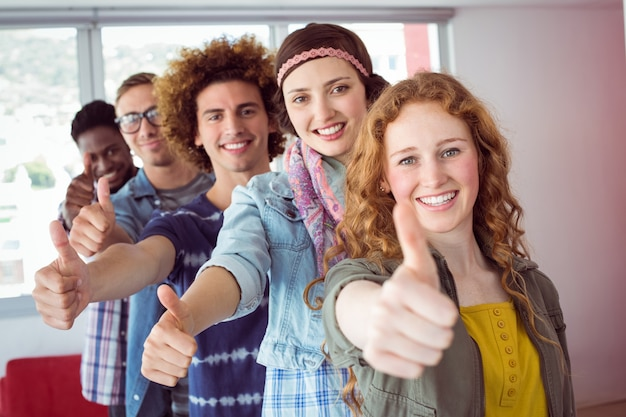 Students smiling in a single line with thumbs up